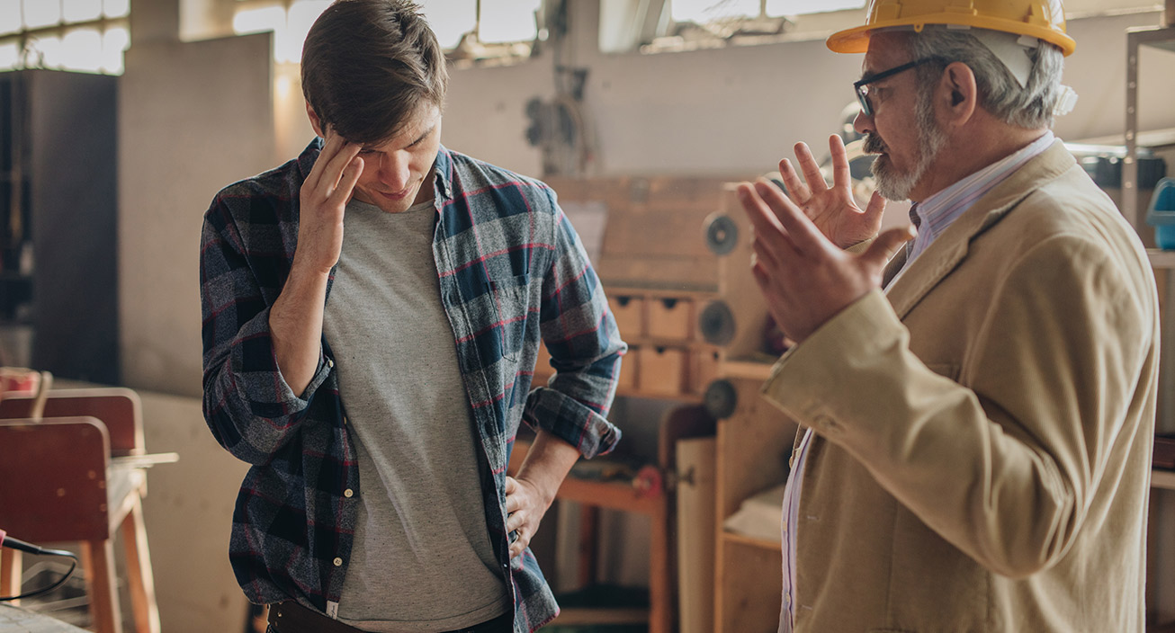 An older employee with a hard hat explains something to a younger employee at a construction business