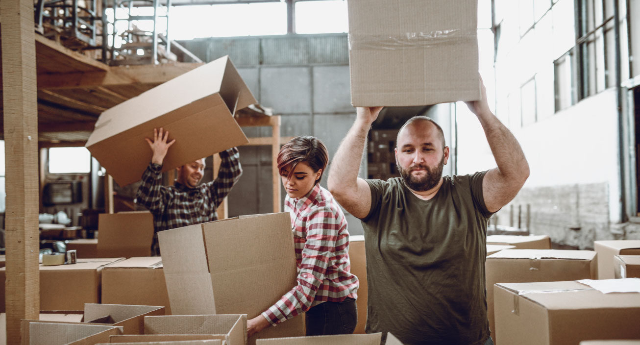 Employees move boxes out of a small business warehouse