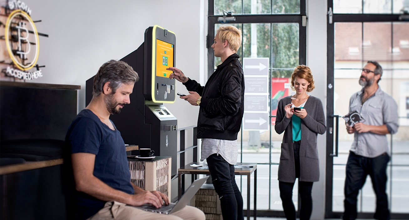 Customers stand at a bitcoin ATM.