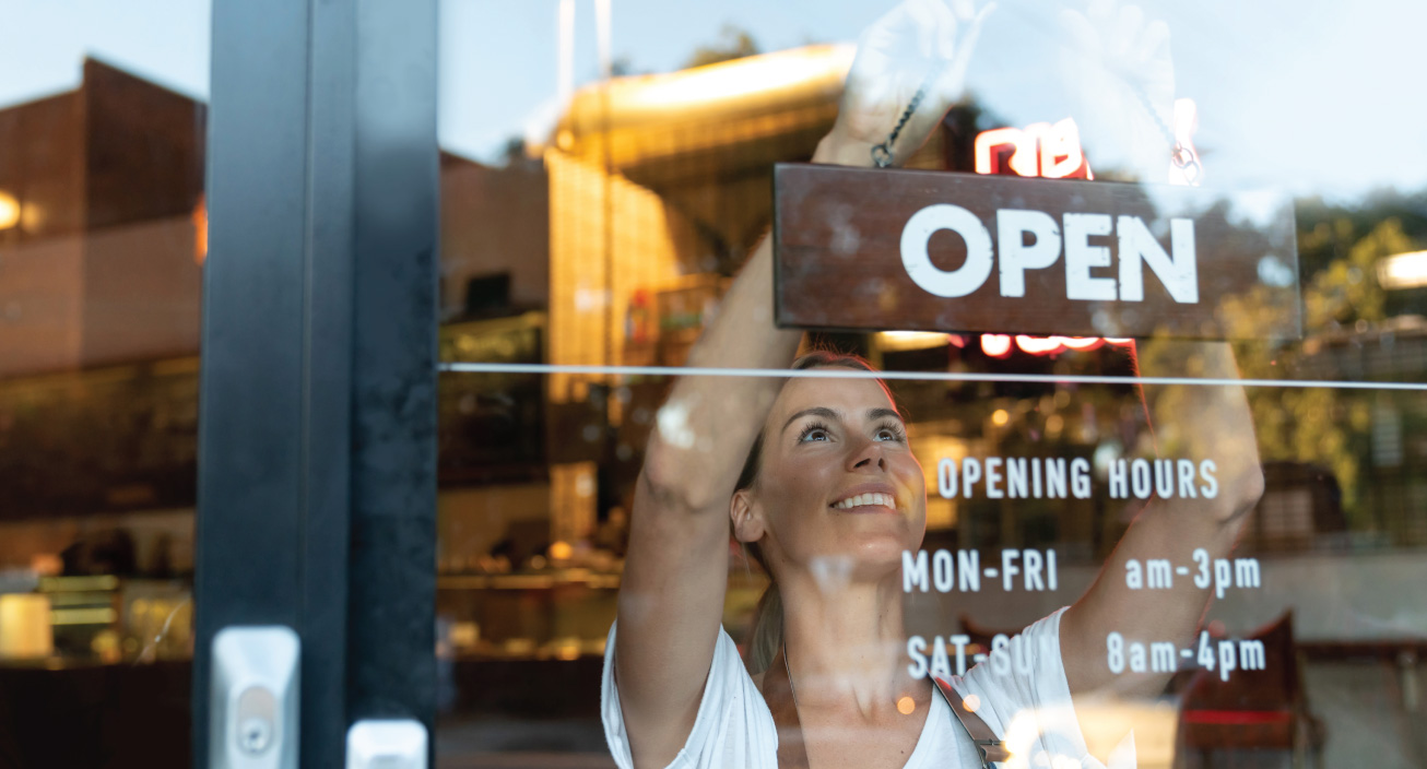 A woman hangs an open sign on her small business.
